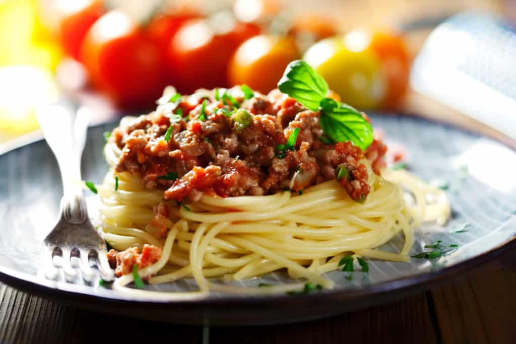 bolognese sauce on top of spaghetti shot from a low angle