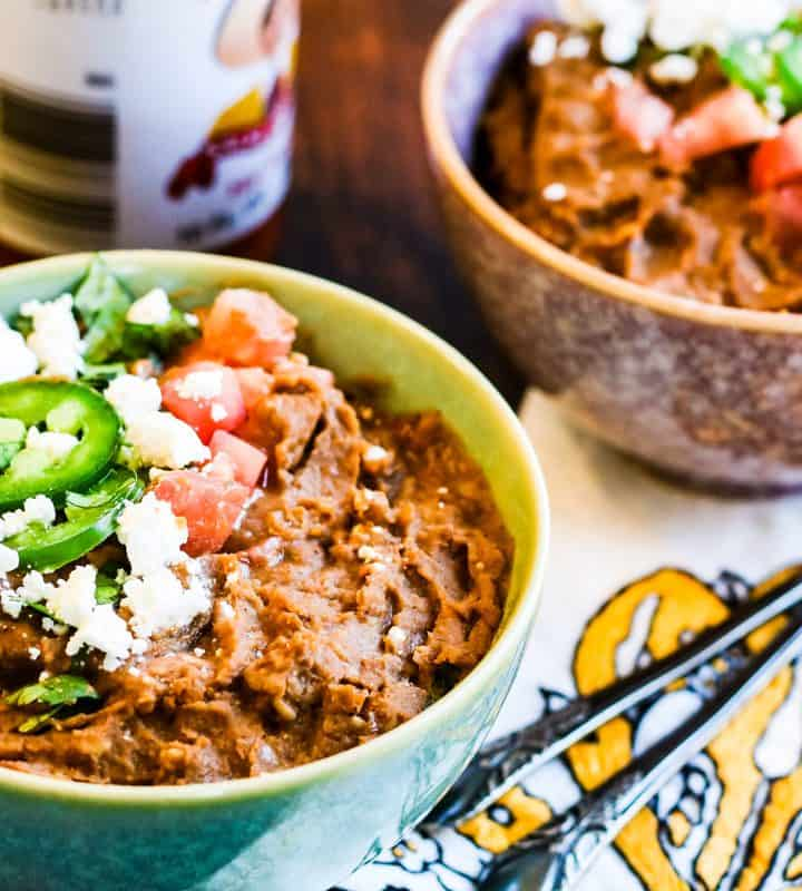 refried beans in bowls topped with cheese, sliced jalapeno, and tomatoes
