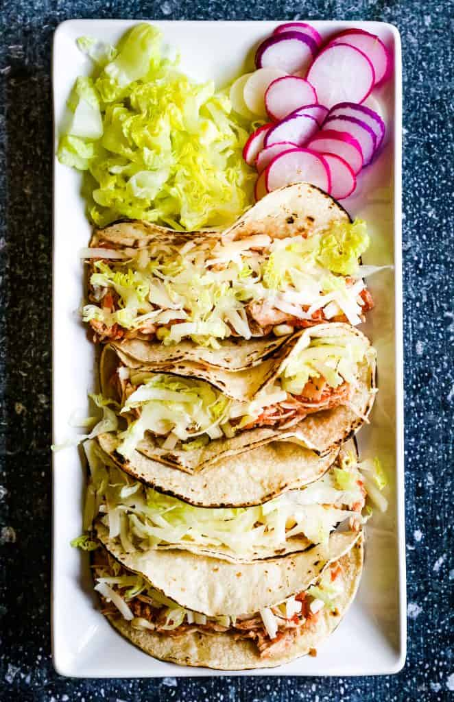 overhead shot of 4 shredded chicken tacos with shredded cheese, lettuce, and sliced radishes on a rectangular white plate.
