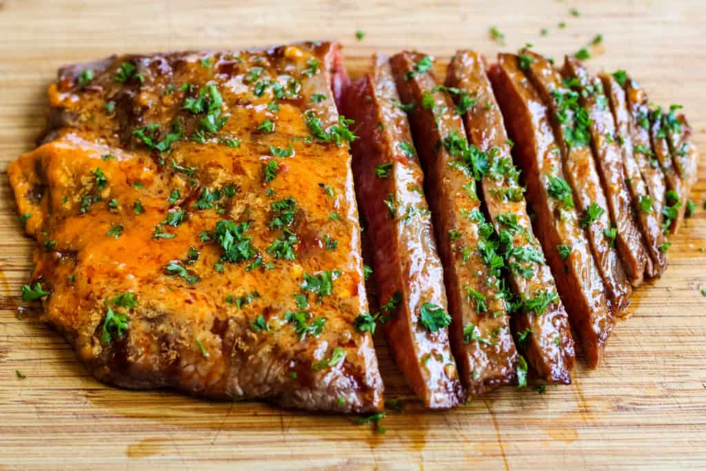 grilled flank steak with chile butter on a cutting board. The photo is shot from overhead. The steak is sliced thinly.
