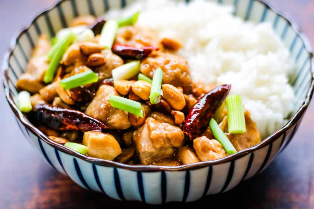 kung pao chicken with red chiles, peanuts, and scallions in a bowl with steamed white rice.