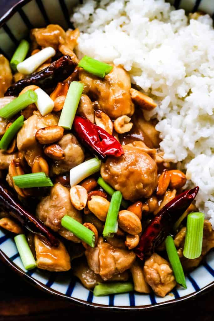 Overhead photo of kung pao chicken in a blue and white striped bowl. The chicken is cooked with red chiles, scallions, and peanuts and served alongside white rice.