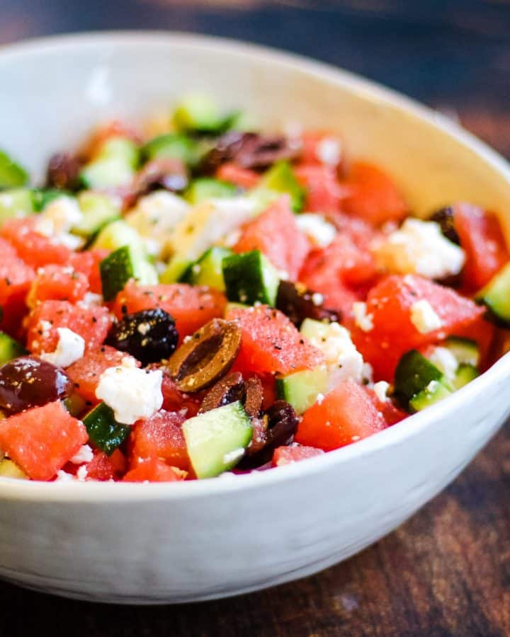 Watermelon and feta salad with cucumbers and kalamata olives in a white bowl