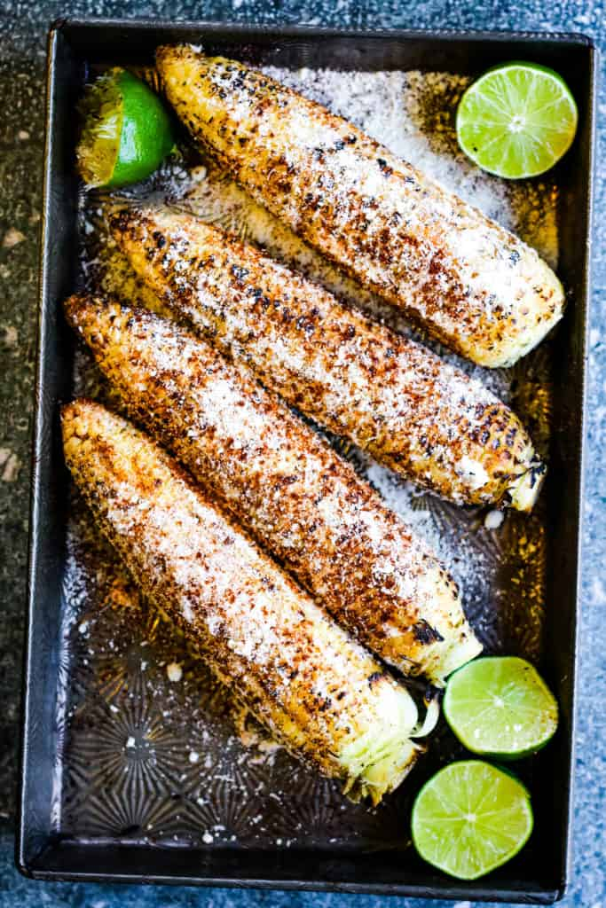 Overhead vertical shot of grilled Mexican corn with limes, cobs are coated with mayonnaise and sprinkled with chili powder and grated cheese