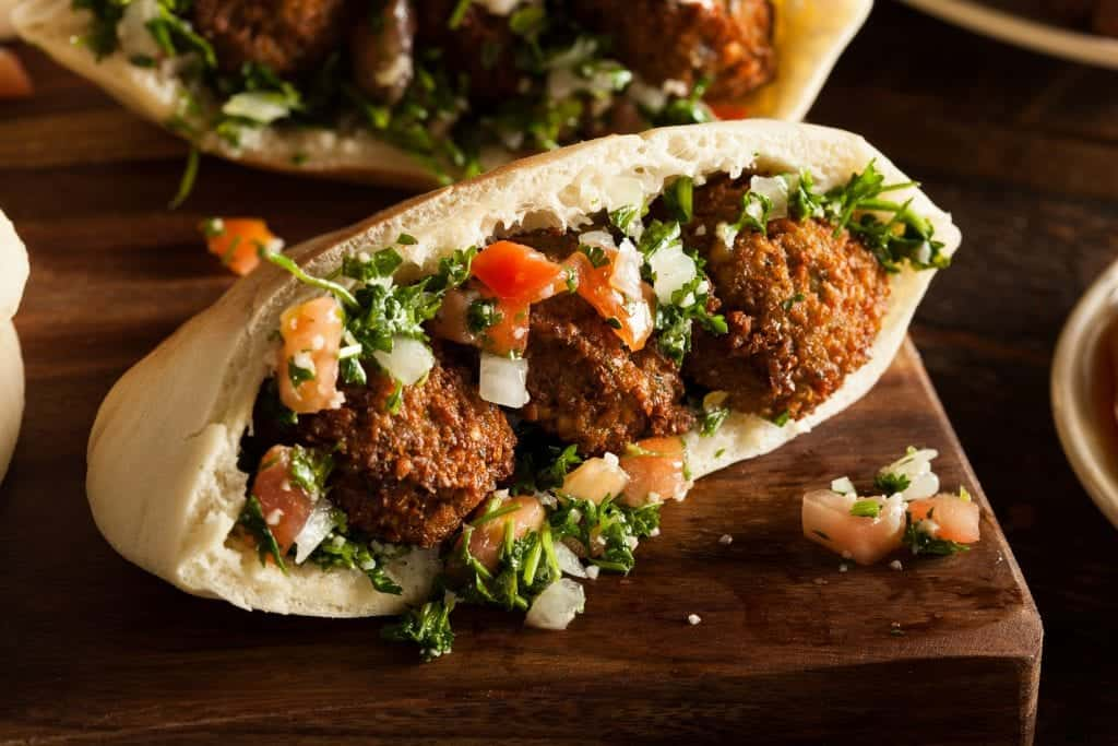 horizontal shot of of an instant pot falafel sandwich with three falafel balls, onions, tomatoes, and parsley in pita bread