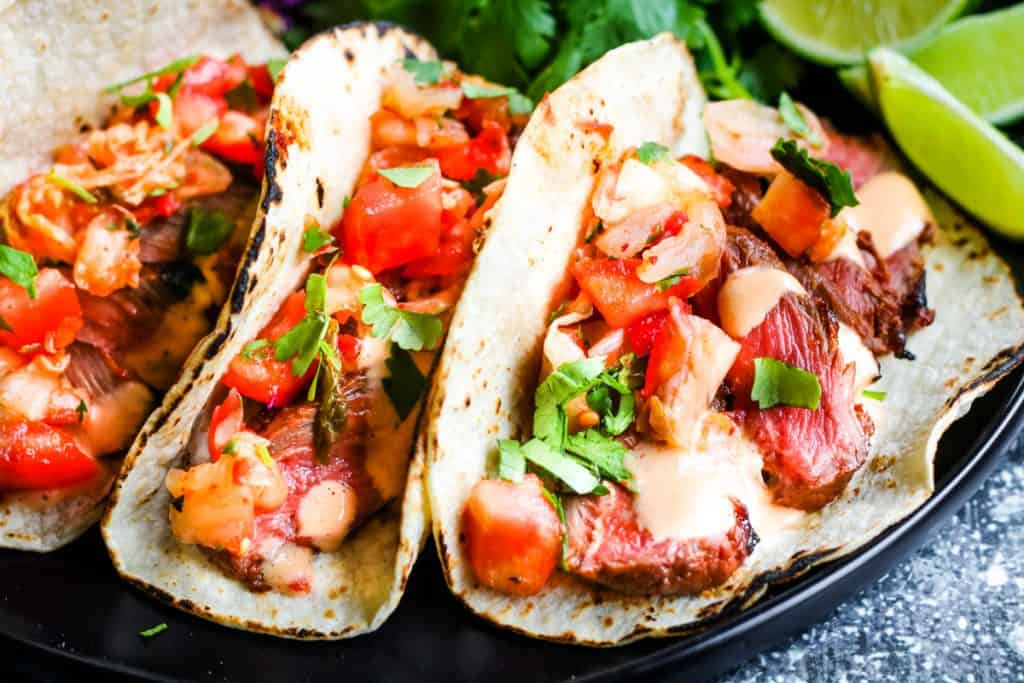 horizontal shot of 3 korean tacos: corn tortillas filled with sliced steak, kimchi and pico de gallo salsa, and chopped cilantro. In the background are lime wedges, sliced red cabbage, and cilantro leaves.