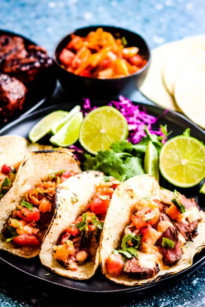 vertical shot of 3 korean tacos: corn tortillas filled with sliced steak, kimchi and pico de gallo salsa, and chopped cilantro. In the background are lime wedges, sliced red cabbage, and cilantro leaves.