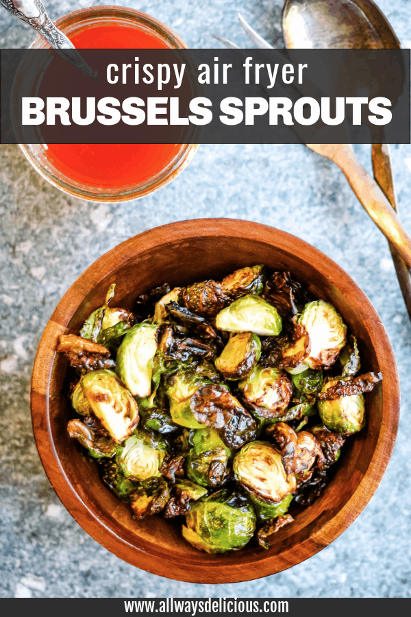 Pinterest pin for air fryer fried brussels sprouts. Text says crispy air fryer brussels sprouts. image is an overhead shot of browned brussels sprouts in a wooden bowl on a stone counter top. there is a jar of harissa dressing and a pair of silver salad serves on the table next to the bowl.