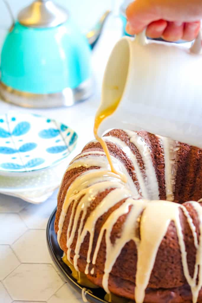 Pumpkin spice bundt cake with a coffee glaze being poured over the top.