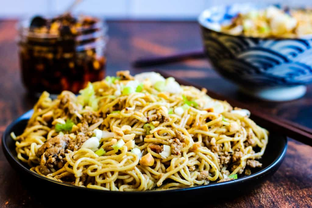 low-angle shot of chinese sesame noodles on a black plate. Next to it is a blue and white serving bowl with sesame noodles in it. There is also a jar of chile crisp. The table is dark brown wood.