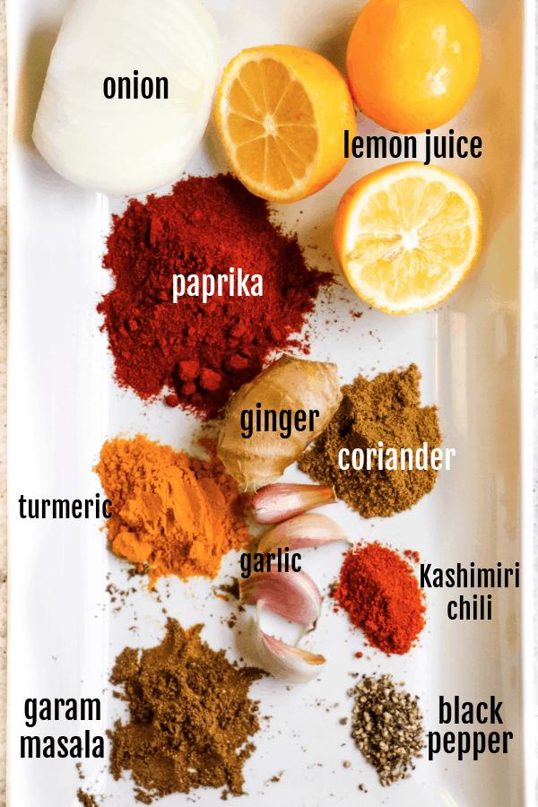 overhead shot of the ingredients needed to make tandoori paste, including onion, lemons, paprika, ginger, coriander, turmeric, garlic, kashmiri chili powder, and garam masala.