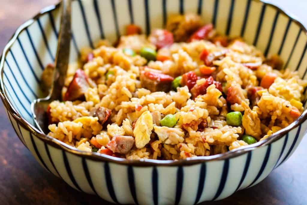 pork fried rice in a white-and-blue striped bowl with a silver serving spoon.