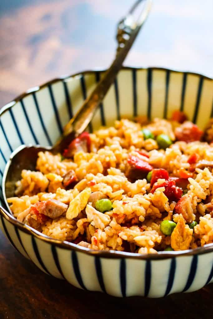fried rice in a blue-and-white striped bowl on a wooden tableThe photo is shot from a low angle.