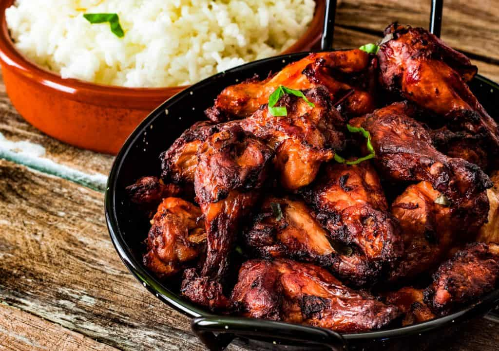 A plate of tandoori chicken with a side dish of cooked rice, shot from a low angle.
