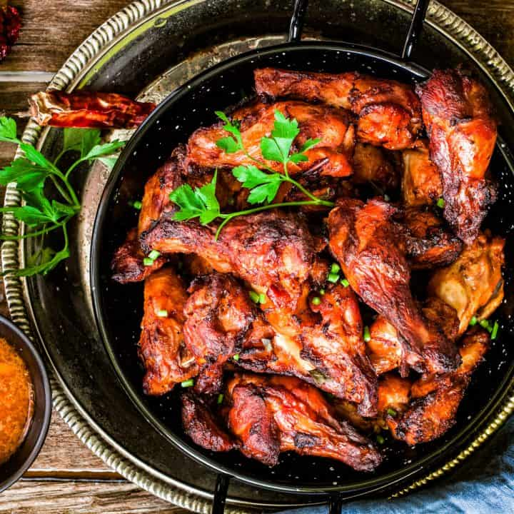 A plate of tandoori chicken with a side dish of chutney. The plate is garnisehd with dried chiles and flat-leaf parsley. The image is shot from overhead.