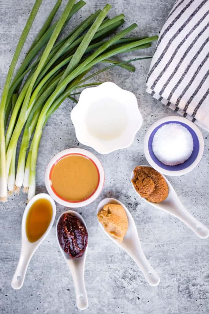 overhead shot of ingredients for miso ramen tare: sesame oil, goghujang, white miso paste, red miso paste, salt, rice vinegar, and sesame paste. There is also a bundle of green onions on the table next to the ingredients.