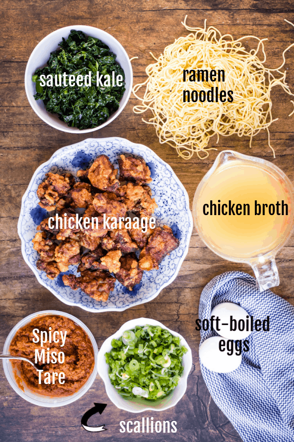 overhead shot of ingredients for spicy miso ramen: sauteed kale, ramen noodles, chicken karaage, chicken broth, spicy miso tare, scallions, and soft boiled eggs.