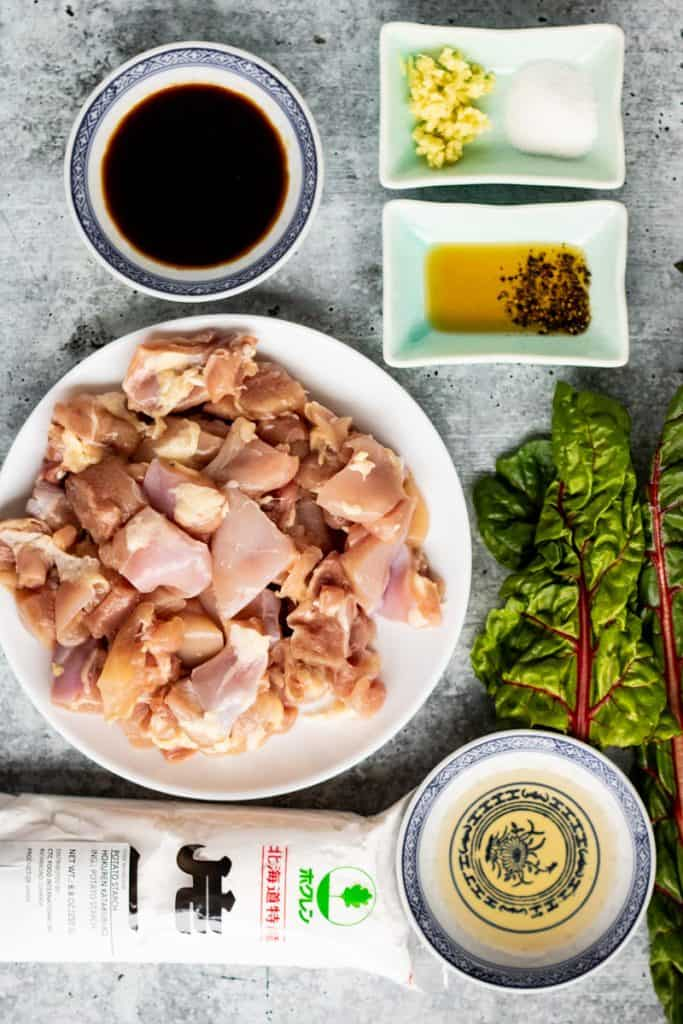 ingredients for chicken karaage shot from overhead. Ingredients include soy sauce, ginger, sugar, sesame oil, rice vinegar, potato starch, and chicken. There are some kale leaves on the side.