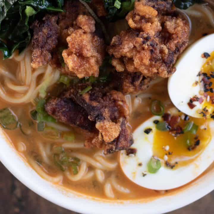 Closeup overhead shot of a bowl of spicy miso ramen topped with chicken karaage, or Japanese fried chicken, soft boiled egg, and sauteed kale.