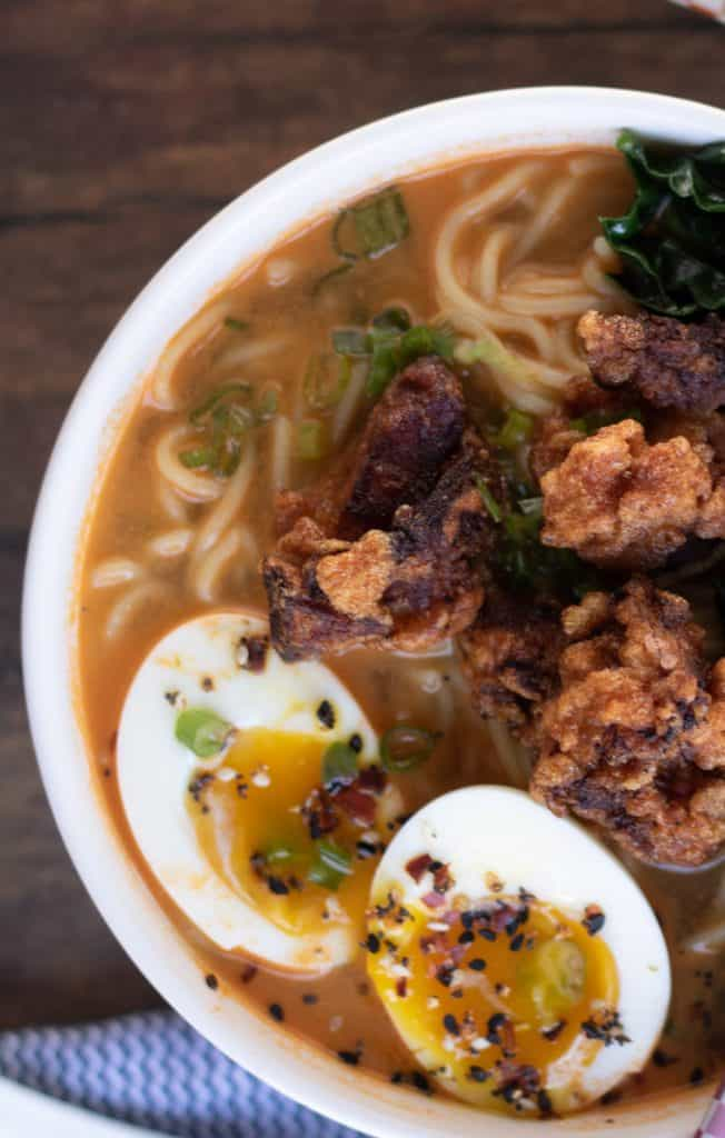 overhead shot of a bowl of spicy miso ramen topped with chicken karaage, or Japanese fried chicken, soft boiled egg, and sauteed kale.